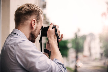 young male photographer with a mirrorless camera.