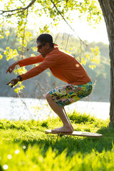Man is training on the balance board on a green meadow