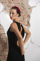 Sexy young girl in a long black dress with heels, with red lips and an attractive smile floral rim in her hair poses in the loft studio intimately taking off the dress