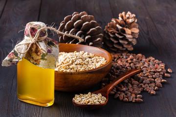 A glass of cedar wood oil. Cedar wood nut in the background