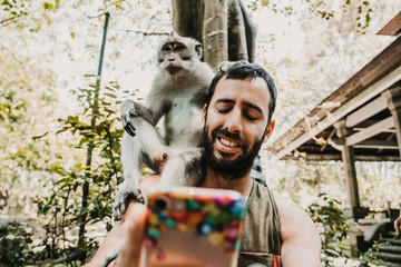 .Young handsome man taking himself some pictures with a cute monckey in the monckey forest in Ubud, Bali. Lifestyle. Travel photography