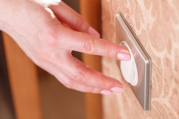 Hand presses the light switch on the wall