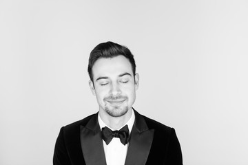 Young handsome man in a tuxedo,  looking at the camera