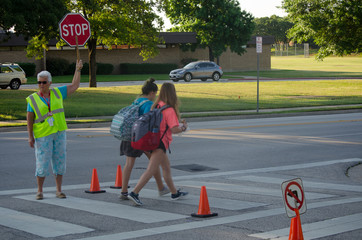 Two Young Girls Going to School at Intersection with School Crossing Guard