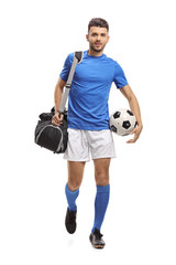 Soccer player with a bag and a football walking towards the camera