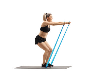 Young woman standing on a mat and exercising with a rubber band