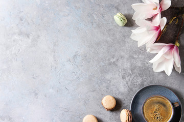 Blue cup of black espresso coffee, french dessert macaroons and spring flowers magnolia branches over grey texture background. Top view, space. Spring greeting card, wallpapers