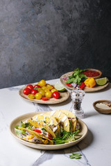 Variety of vegetarian corn tacos with vegetables, green salad, chili pepper served on ceramic plate with tomato and cream sauces with ingredients above on white marble kitchen table