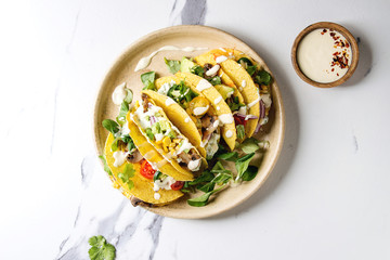 Variety of vegetarian corn tacos with vegetables, green salad, chili pepper served on ceramic plate with cream sauce over white marble background. Top view, copy space.