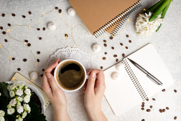 Flat lay feminine background with coffee cup, notebooks and flower hyacinth. Female hands holding coffee cup. Cozy weekend at home concept. Top view