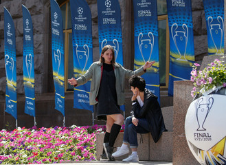 Women rest next to flags with the UEFA Champions League final logo in Kiev