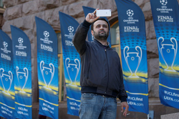 A man takes a picture in a front of flags with the UEFA Champions League final logo in Kiev