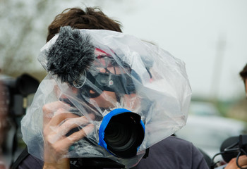 Video operator journalist filming an event during the rain with a plastic bag wrapped around his camera. Concept of pritecting the gear from getting wet