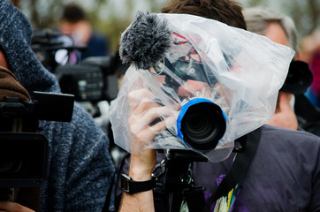 filming,plastic bag,plastic,video camera,video,camera,rain,wet,game,cover,photographer,water,protection,isolated,football,match,adult,closeup,light,travel,lifestyle,technology,hand,studio,new,outdoors
