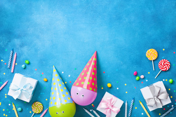 Holiday background with funny balloons in caps, gifts, confetti, candy and candles. Flat lay. Birthday or party greeting card with copy space.