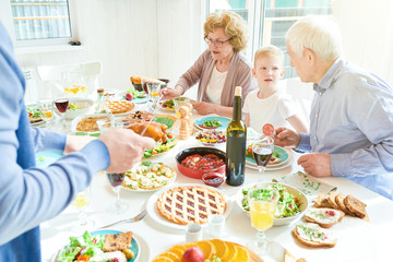 Portrait of happy family enjoying dinner together sitting round festive table with delicious dishes during holiday celebration, two grandparents and little boy in modern sunlit apartment, copy space