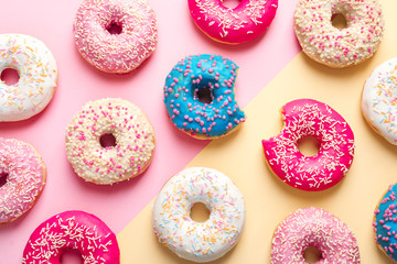 Delicious glazed doughnuts on color background, top view