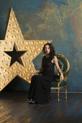A sexy girl with red lips in a luxurious black dress and high heels poses in a rich studio interior with gold and a light star