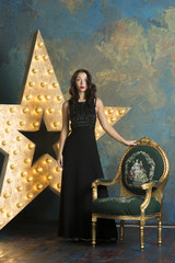 A sexy girl with red lips and curly hair in a luxurious black dress and high heels poses in a rich studio interior with gold and a light star