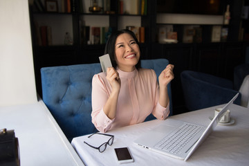 Smiling business woman looking up and smiling. Holding credit card. Received project money.