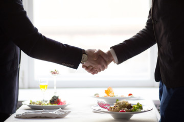 Close up of handshaking of two business people standing at table at restaurant.