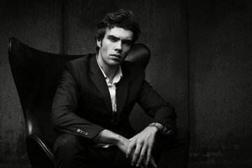 Stylish young man sitting in a chair. Black jacket and white shirt.