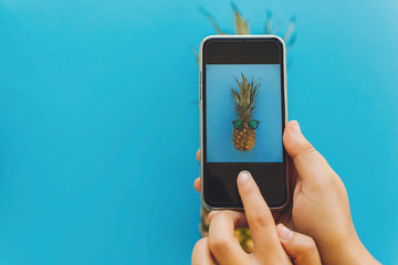 instagram blogging workshop concept. hands holding phone and taking photo of pineapple in stylish sunglasses on blue trendy paper background, flat lay. space for text.