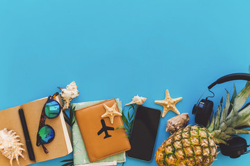summer vacation and travel flat lay. stylish black phone, passport, sunglasses, map, pineapple with headphones, shells,notebook on trendy blue paper. space for text.  wanderlust