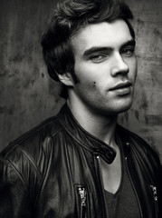 Closeup of a beautiful young man in black leather jacket. Contrast black and white portrait
