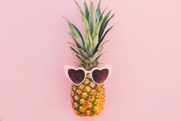 stylish pineapple in pink sunglasses on trendy pink paper background. flat lay. summer vacation and...