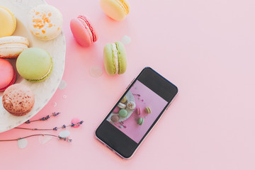modern food photography concept. phone with photo of stylish colorful macaroons in vintage plate on trendy pink paper with lavender. space for text. instagram blogging concept
