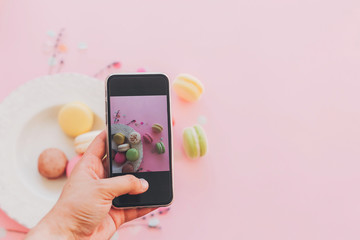 instagram blogging concept, flat lay. food photography. hand holding phone and taking photo of stylish colorful macaroons in vintage plate on trendy pink paper. space for text
