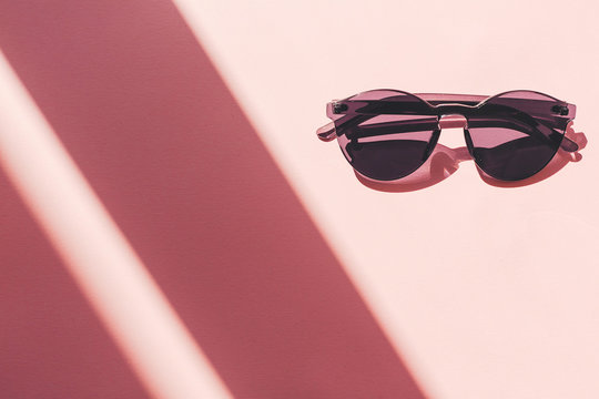 summer vacation and party concept. stylish black sunglasses on trendy pink paper background in sun light. flat lay. space for text. travel and wanderlust concept.