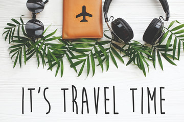 It's Travel Time text on passport with plane, retro sunglasses and headphones on green palm leaves on white wood. modern travel and summer vacation flat lay