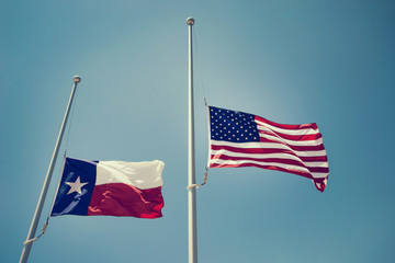 The state flag of Texas and the United States flag flying at half-mast or half-staff on a flagpole. Blue sky background with copy space. Vintage tone.