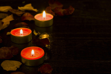 Lighted candle on the background of a large number of wilted leaves