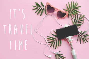 It's Travel Time text on stylish pink sunglasses, phone on selfie stick, headphones, and green palm leaves on pink background. summer vacation flat lay. time to travel