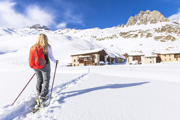 Young girl walks with snowshoes near the village of Grevasalvas, Engadin Valley, Graubünden, Switzerland, Europe.