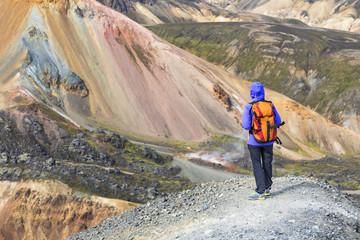 A trekker is looking at the Landmannalaugar panorama from the Blahnukur mountain (Landmannalaugar, Fjallabak Nature Reserve, Highlands, Southern Region, Iceland, Europe)