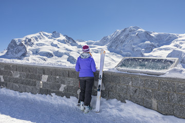 A skier is looking the Monte Rosa Massif from Gornergrat's view point (Zermatt, Canton of Valais, Visp, Switzerlan, Europe)