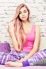 Young woman with long pink hair sitting on bed wearing pajamas. Closeup, studio lighting, retouched.