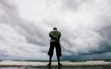 A man looks at the rough sea as rainy clouds gather above during the monsoon period in Colombo