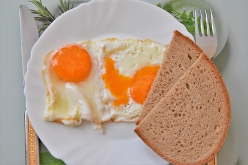 fried eggs on a white plate with bread, fork and knife