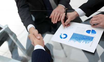 handshake of financial partners at the Desk