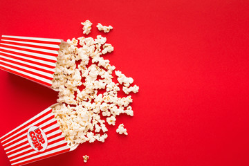 Bucket of popcorn on red background, top view