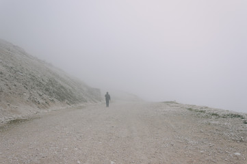 Man walking in the fog. Misty dirt road in mountains