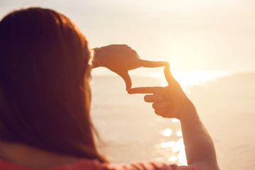 Future planning, Close up of woman hands making frame gesture with sunrise on sea summer, Female capturing the sunrise, sunlight outdoor.