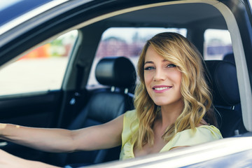Attractive young woman driving a car.