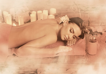 Massage of woman in spa salon. Girl on candles background in herbal steam room. Luxary interior in oriental therapy salon. Female have relax after sport. Old photo effect with sepia.