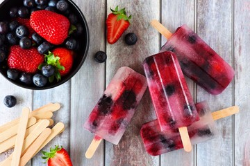 Healthy berry fruit popsicles on a rustic wood background. Top view scene.
